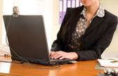 Business woman sitting in the office in front of the laptop — Stock Photo