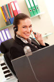 Young business woman working on computer and wearing headphones — Stock Photo