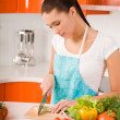 Stock Photo: Young woman cutting vegetables in a kitchen