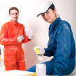 Construction workers at work, preparing to paint — Stockfoto