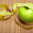 Green apple with centimeter tape — Stock Photo