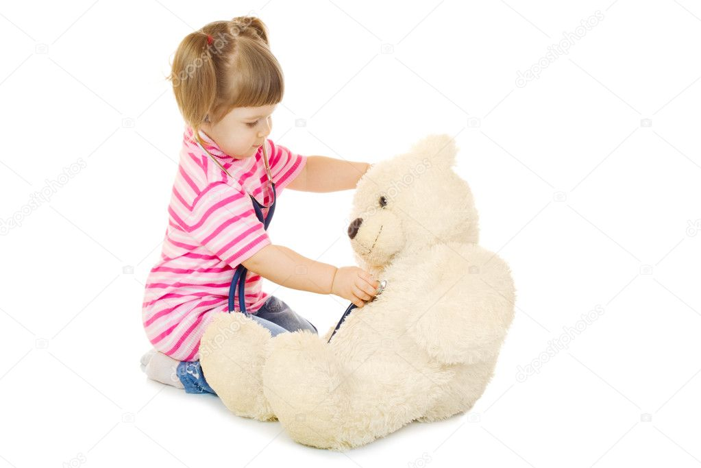 Little girl listens a stethoscope to a toy bear isolated  Stock Photo #5791011