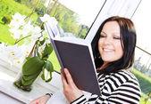 Kvinna läsa bok i huset — Stockfoto