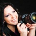 Photographer woman holding camera over dark background — Stock Photo