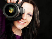 Photographer woman holding camera over dark background — Stock Photo