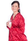 Woman in pajamas with glass of milk — Stockfoto