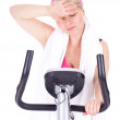 Girl on stationary training bicycle - Stockfoto