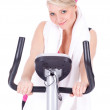 Girl on stationary training bicycle — Stock Photo