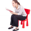 Reading woman sitting on the small chair — Stock Photo