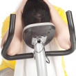 Overweight woman on fitness bicycle — Stock Photo