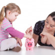 Little girl with woman and piggy bank — Stok fotoğraf