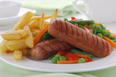 Sausage with french fries and vegetables — Stock Photo