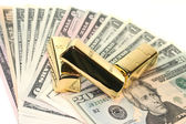 Gold bullion on dollar bills — Stock Photo