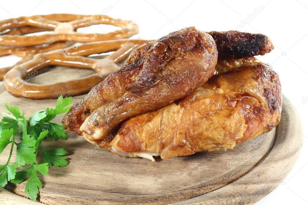 欧芹和脆饼干在木板上的烤鸡