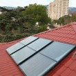Solar panel (geliosystem) on the red roof. - Stock Photo