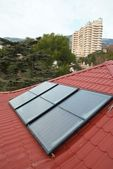 Solar panel (geliosystem) on the red roof. — Stock Photo