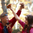 Young couple enjoying the falling leaves — Stock Photo