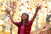 Beautiful girl with falling leaves — Stock Photo