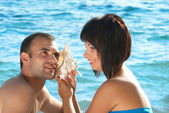 Young couple with seashell — Stock Photo