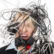 Mature businesswoman's screaming in cables. — Stock fotografie