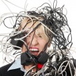 Mature businesswoman&#039;s screaming in cables. - Stock Photo