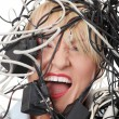 Mature businesswoman's screaming in cables. - Stock Photo