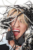 Mature businesswoman's screaming in cables. — Stock Photo