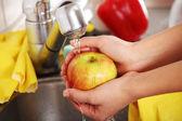 Woman hands washing apple — Stock Photo