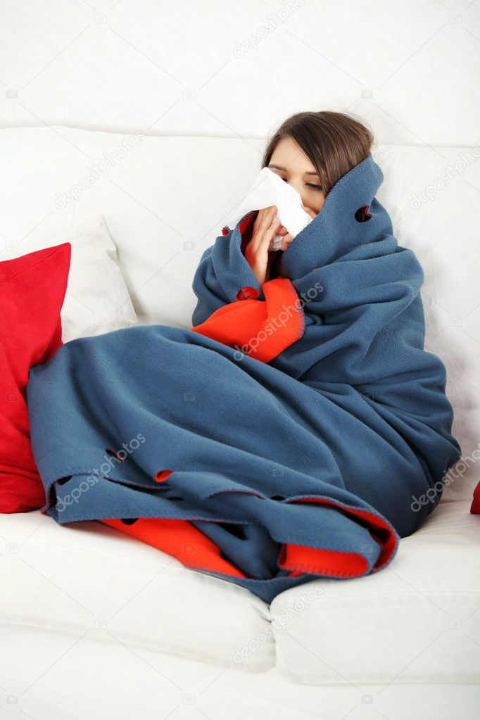 Young woman at home having flu, wrapped up in blanket, sneezing. — Stock Photo #5795204