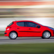 Blur small red economical family compact city car — Stock Photo