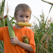 Boy with the corn in his teeth — Stock Photo