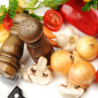 Salt and pepper shakers, vegetables, knife on table — Stock fotografie