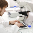 Young male researcher looking into a microscope and writing notes on laptop — Stock Photo