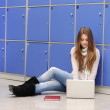 Beautiful female student sitting on ground with laptop — Stock Photo
