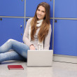 Beautiful female student sitting on ground with laptop and leaning on locke — Stock Photo