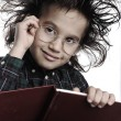 Smart nerd kid with glasses and funny hair writing — Stock Photo