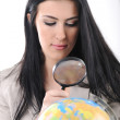 Young beautiful woman with magnifier searching on Earth map, globe — Stockfoto