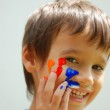 Kid with color on his fingers and face — Stock Photo