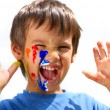 Kid with color on his fingers and face yelling — Stock Photo