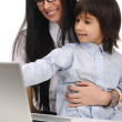 Happy mother and son on laptop at the table — Stock Photo