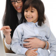 Happy young beautiful mother and cute little son on laptop at the table — Stock Photo