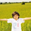 Happy kid in nature, positive smiling child on green beautiful meadow with — Stock Photo