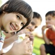Stockfoto: Small group of children in nature eating snacks together, sandwiches, bread
