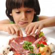 Cute positive boy and raw meat and vegetables in plate reading for cooking — Stock Photo #6150484