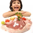 Cute positive boy and raw meat and vegetables in plate reading for cooking — Stock Photo