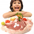 Cute positive boy and raw meat and vegetables in plate reading for cooking — Stock Photo #6150489