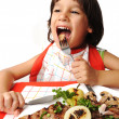 Cute positive boy with fork and knife eating on lunch table — Stock Photo