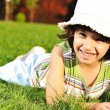 Cute kid with hat on head laying on grass in park — Stock Photo
