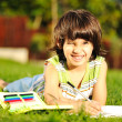 Stock Photo: Boy doing home work outdoors