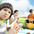 Happy group of children outdoor on meadow: eating and playing together — Stock Photo #6150564